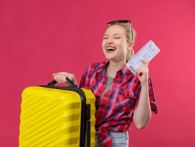 Молодая девушка путешественника с закрытыми глазами в красной рубашке в очках держит чемодан и билет на изолированном розовом фоне