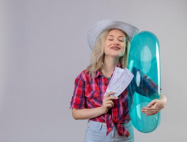 Молодая девушка путешественника с закрытыми глазами в красной рубашке в шляпе держит надувное кольцо и билеты на изолированном белом фоне