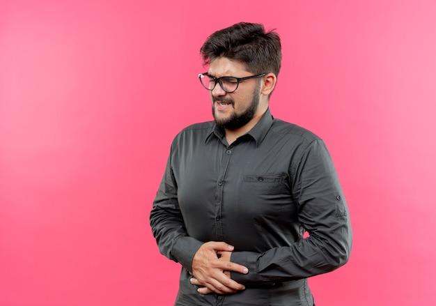 Con gli occhi chiusi il giovane uomo d'affari che indossava gli occhiali ha afferrato lo stomaco dolorante isolato su sfondo rosa