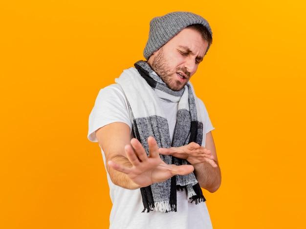 눈을 감고 불쾌한 젊은 아픈 사람이 겨울 모자와 스카프를 착용하고 노란색에 고립 된 카메라에서 손을 잡고