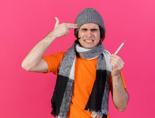 Con gli occhi chiusi dispiaciuto giovane uomo malato che indossa cappello invernale con sciarpa tenendo il termometro che mostra il suicidio con il gesto della pistola isolato su sfondo rosa