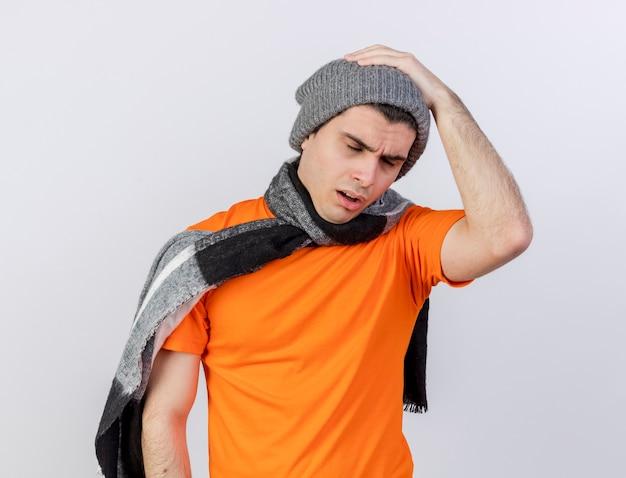Con gli occhi chiusi dispiaciuto giovane uomo malato che indossa il cappello invernale con sciarpa mettendo la mano sulla testa dolorante isolata su bianco