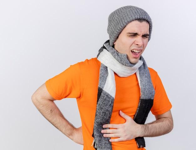 흰색 배경에 고립 된 아픈 위장에 손을 넣어 스카프와 겨울 모자를 쓰고 눈을 감고 불쾌한 젊은 아픈 남자