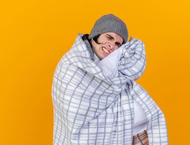 Con gli occhi chiusi dispiaciuto giovane uomo malato che indossa cappello invernale con sciarpa avvolta in un plaid isolato sull'arancio