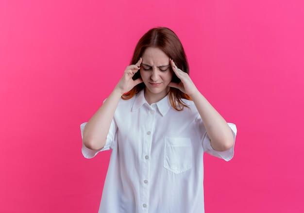 С закрытыми глазами недовольная молодая рыжая девушка кладет руки на храм на розовом фоне