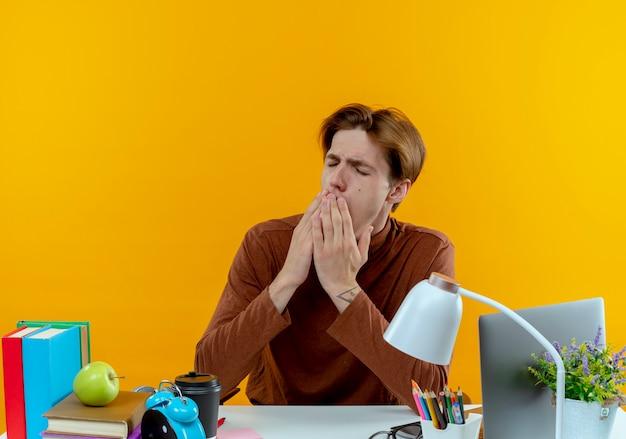 닫힌 눈으로 학교 도구로 책상에 앉아 불쾌한 젊은 학생 소년이 노란색에 손으로 입을 덮었습니다.