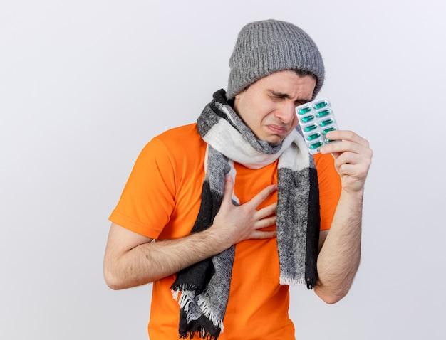 Con gli occhi chiusi debole giovane uomo malato che indossa il cappello invernale con sciarpa tenendo le pillole e mettendo la mano sul petto dolorante isolato su sfondo bianco