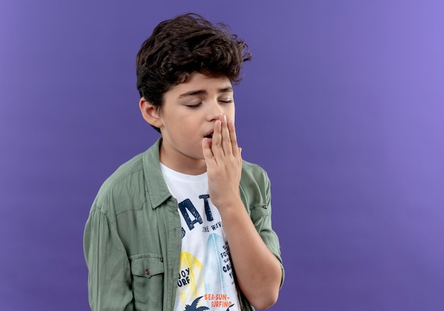 With closed eyes yawning little schoolboy covered mouth with hand isolated on purple wall with copy space