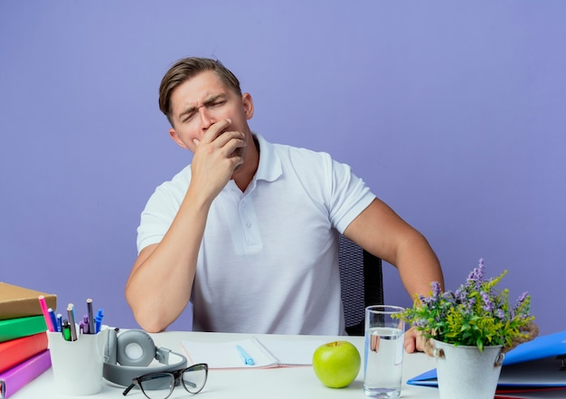 With closed eyes yawning young handsome male student sitting at desk with school tools covered mouth with hand isolated on blue