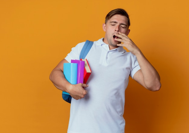 With closed eyes yawning young handsome male student wearing back bag holding books