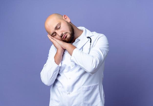 目を閉じて、青い背景で隔離の睡眠ジェスチャーを示す医療ローブと聴診器を身に着けている若いハゲ男性医師