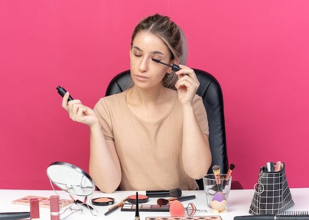 With closed eyes young beautiful girl sits at table with makeup tools applying mascara isolated on pink background