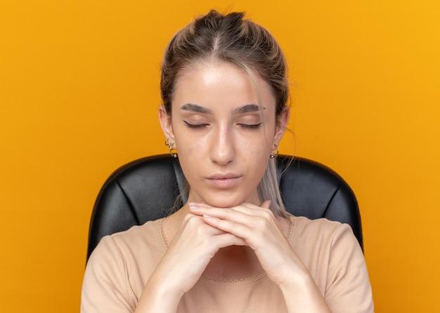 Con gli occhi chiusi la giovane bella ragazza si siede alla tavola con gli strumenti di trucco che mettono la mano sotto il mento isolato su fondo arancio