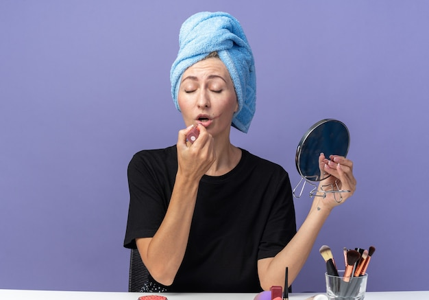 With closed eyes young beautiful girl sits at table with makeup tools wiping hair in towel applying lipstick holding mirror isolated on blue background