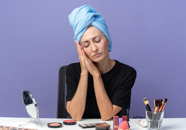 With closed eyes young beautiful girl sits at table with makeup tools wiping hair in towel showing sleep gesture isolated on blue background
