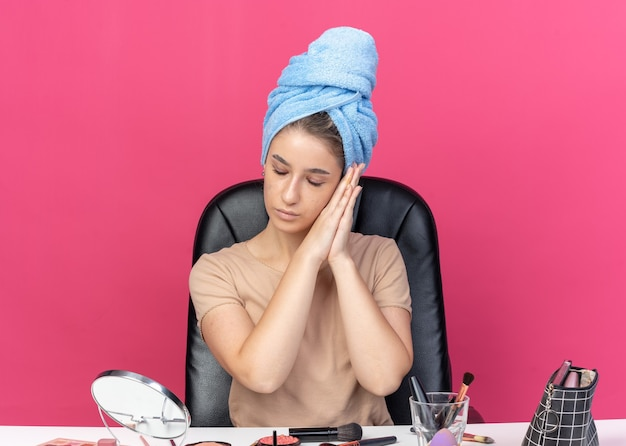 With closed eyes young beautiful girl sits at table with makeup tools wrapped hair in towel showing sleep gesture isolated on pink background
