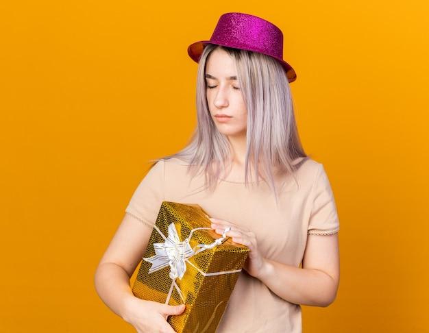 Молодая красивая девушка с закрытыми глазами в партийной шляпе держит подарочную коробку