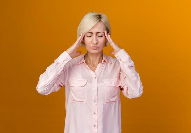 Молодая славянская блондинка с закрытыми глазами кладет руки на храм, изолированные на оранжевом