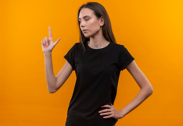 With closed eyes young caucasian girl wearing black t-shirt points to up put her hand on hip on isolated orange wall