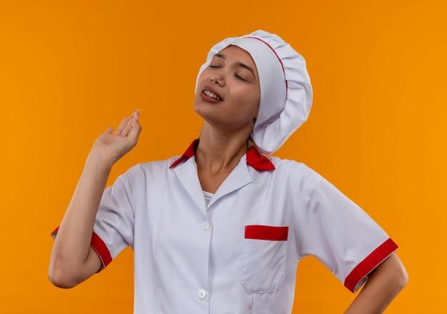 С закрытыми глазами молодая женщина-повар в униформе шеф-повара показывает жест на изолированном оранжевом фоне