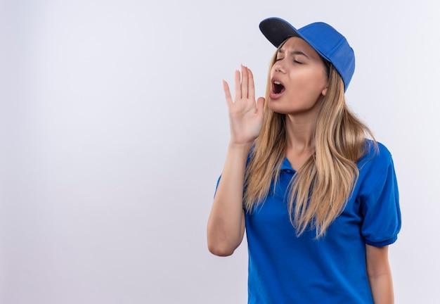目を閉じて青い制服とキャップを身に着けている若い配達の女の子は、コピースペースで白い壁に隔離された誰かを呼び出します