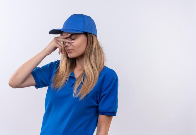 目を閉じて青い制服とキャップを身に着けている若い配達の女の子はコピースペースで白い壁に隔離された目に手を置く