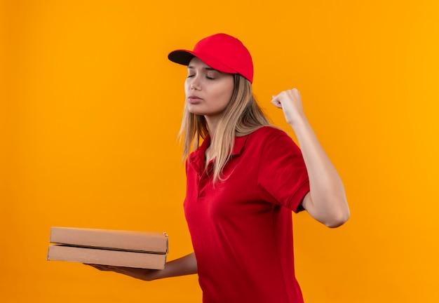 Con gli occhi chiusi la giovane ragazza delle consegne che indossa l'uniforme rossa e il cappuccio - tenendo la scatola della pizza e mostrando il gesto di sì isolato sulla parete arancione