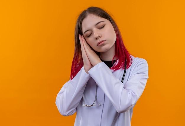 目を閉じて聴診器の医療ローブを身に着けている若い医者の女の子は、孤立したオレンジ色の壁に睡眠ジェスチャーを示しています