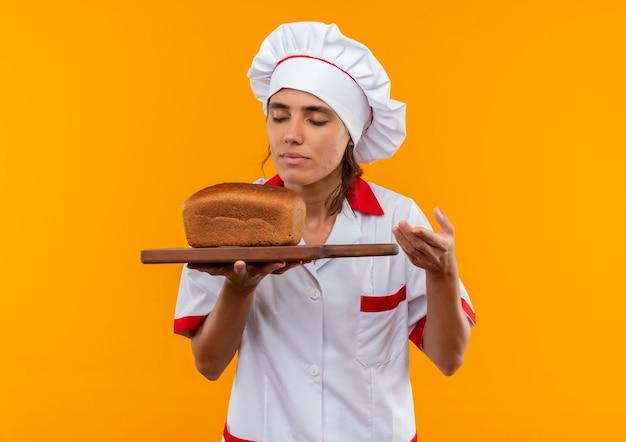 目を閉じて、コピースペースのあるまな板の上でパンを持って嗅ぐシェフの制服を着た若い女性料理人