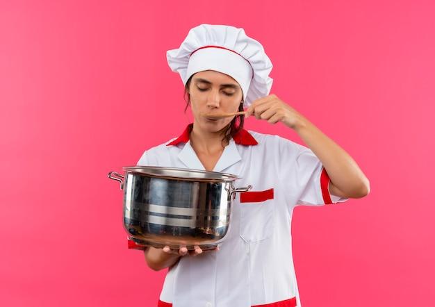 目を閉じて、鍋を持ってコピースペースでスープを試すシェフの制服を着た若い女性料理人