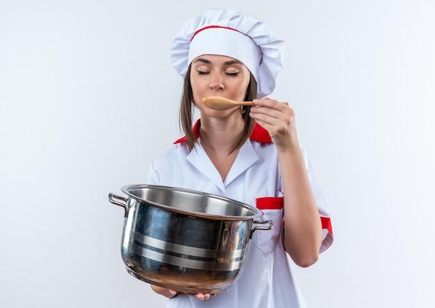 目を閉じて、白い背景で隔離のスプーンでスープを試して鍋を保持しているシェフの制服を着た若い女性料理人