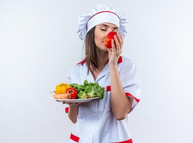 Con gli occhi chiusi, giovane cuoca che indossa l'uniforme da chef che tiene le verdure sul piatto e annusa il pepe in mano isolato su sfondo bianco