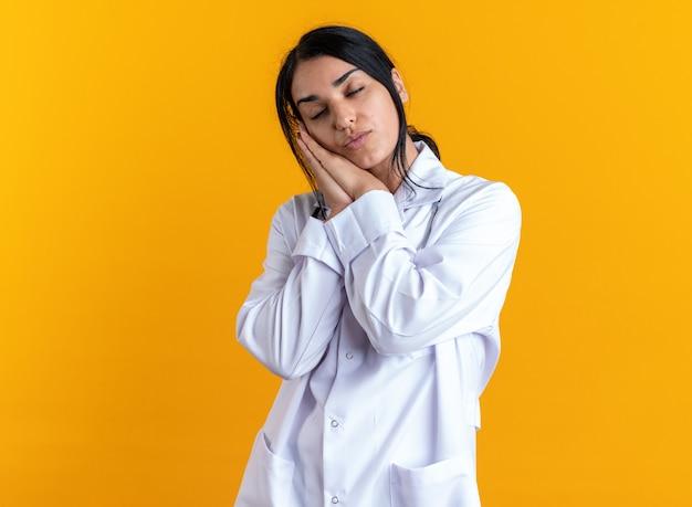 노란색 배경에 격리된 수면 제스처를 보여주는 청진기가 달린 의료 가운을 입은 젊은 여성 의사