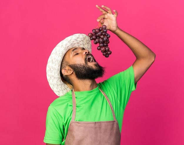 С закрытыми глазами молодой садовник афро-американского парня в садовой шляпе пытается схватить