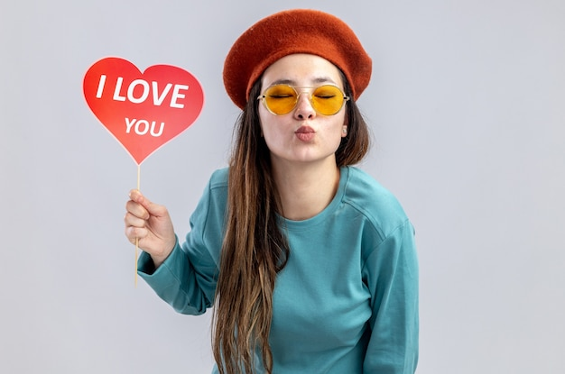 With closed eyes young girl on valentines day wearing hat with glasses holding red heart on a stick with i love you text showing kiss gesture isolated on white background