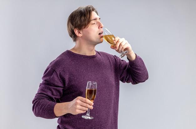 Con gli occhi chiusi giovane ragazzo il giorno di san valentino che tiene e beve bicchieri di champagne isolati su sfondo bianco