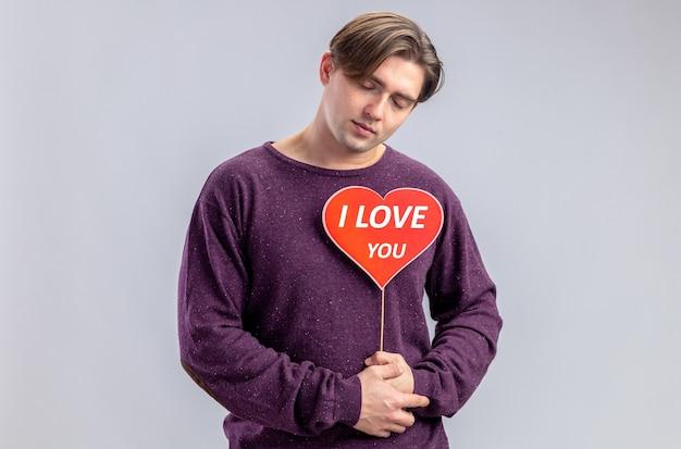 Con gli occhi chiusi giovane ragazzo il giorno di san valentino che tiene il cuore rosso su un bastone con ti amo testo isolato su sfondo bianco