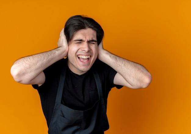 Con gli occhi chiusi giovane barbiere maschio bello in orecchie di chiusura uniformi con le mani isolate sull'arancio
