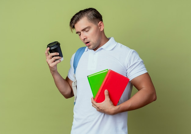 目を閉じて、コーヒーとオリーブグリーンで隔離の本を保持しているバックバッグを身に着けている若いハンサムな男性学生