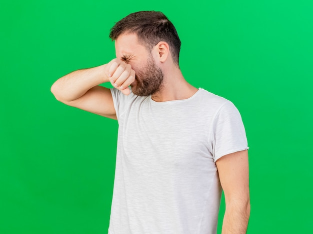 With closed eyes young ill man putting arm on nose isolated on green background