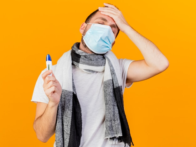 目を閉じて冬の帽子と黄色の背景で隔離の額に手を置く温度計を保持している医療マスクを身に着けている若い病気の男