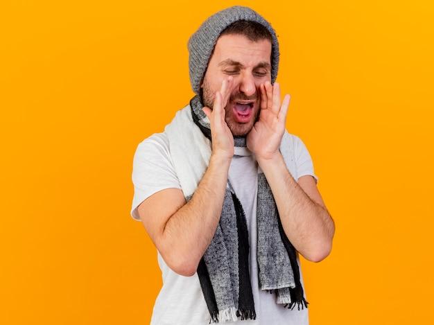 目を閉じて、冬の帽子とスカーフを身に着けている若い病気の男が黄色で孤立した誰かを呼び出します
