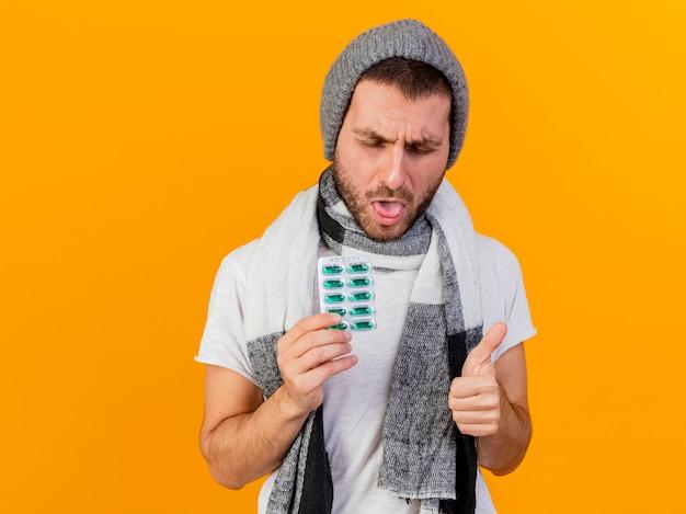 目を閉じて、冬の帽子とスカーフを身に着けている若い病気の人が丸薬を保持し、黄色の背景に分離された親指を示しています