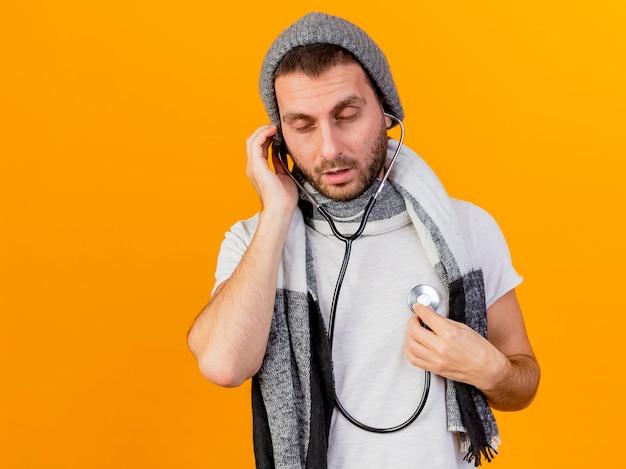 Con gli occhi chiusi giovane uomo malato che indossa cappello invernale e sciarpa ascoltando il proprio battito cardiaco con lo stetoscopio isolato su sfondo giallo