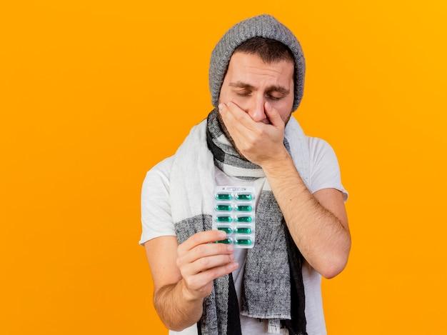 Con gli occhi chiusi giovane uomo malato che indossa cappello invernale e sciarpa mettendo la mano sulla bocca e tenendo fuori le pillole alla telecamera isolata su giallo