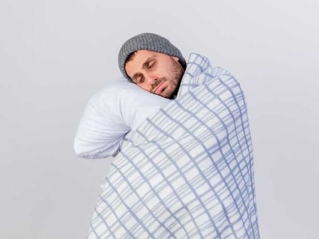 Con gli occhi chiusi giovane uomo malato che indossa cappello invernale e sciarpa avvolta in un plaid abbracciato cuscino