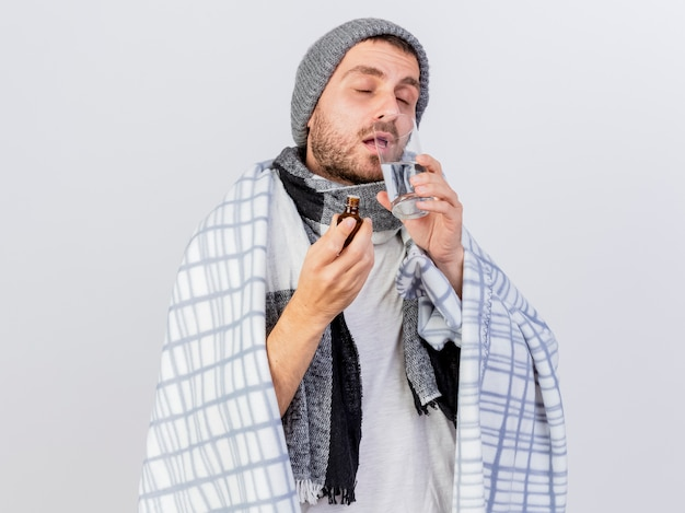 Con gli occhi chiusi giovane uomo malato che indossa cappello invernale e sciarpa avvolto in un plaid isolato su bianco