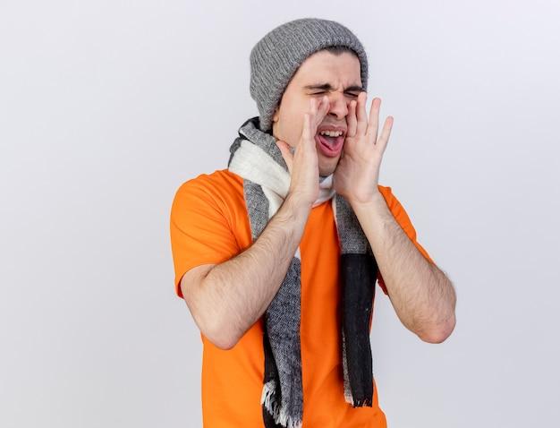 Con gli occhi chiusi giovane uomo malato che indossa il cappello invernale con sciarpa chiamando qualcuno isolato su bianco