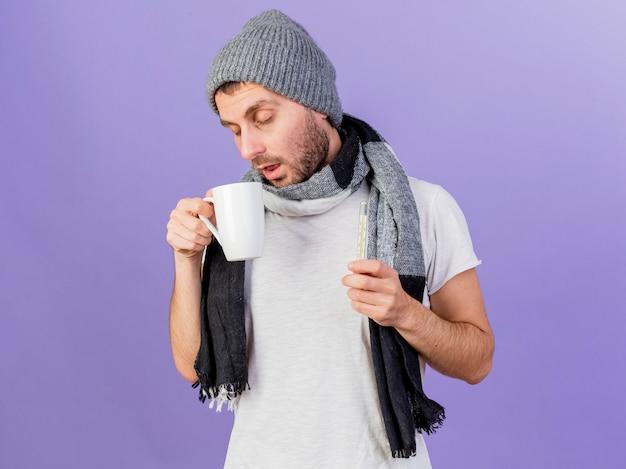 눈을 감고 젊은 아픈 사람이 보라색 배경에 고립 된 차와 온도계의 컵을 들고 스카프와 함께 겨울 모자를 쓰고