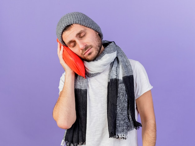 目を閉じて、紫色の背景で隔離の頬に湯たんぽを保持しているスカーフと冬の帽子をかぶって若い病気の男